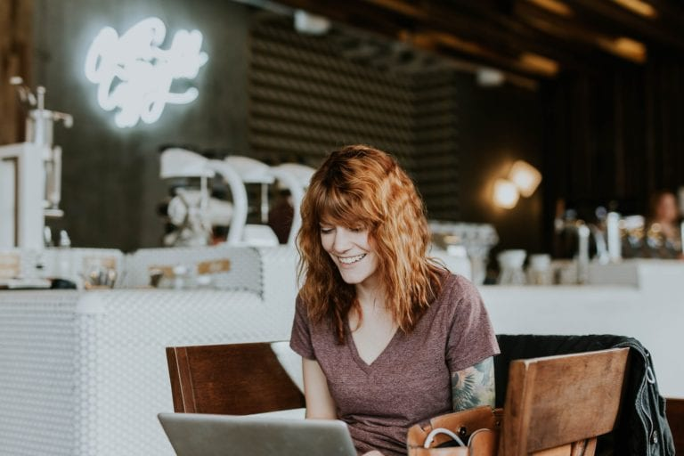 Woman doing digital marketing from coffee shop on Facebook Ads and Facebook Boosted Posts